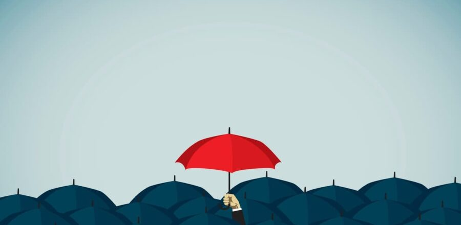 a red umbrella stands out against a sea of black umbrellas