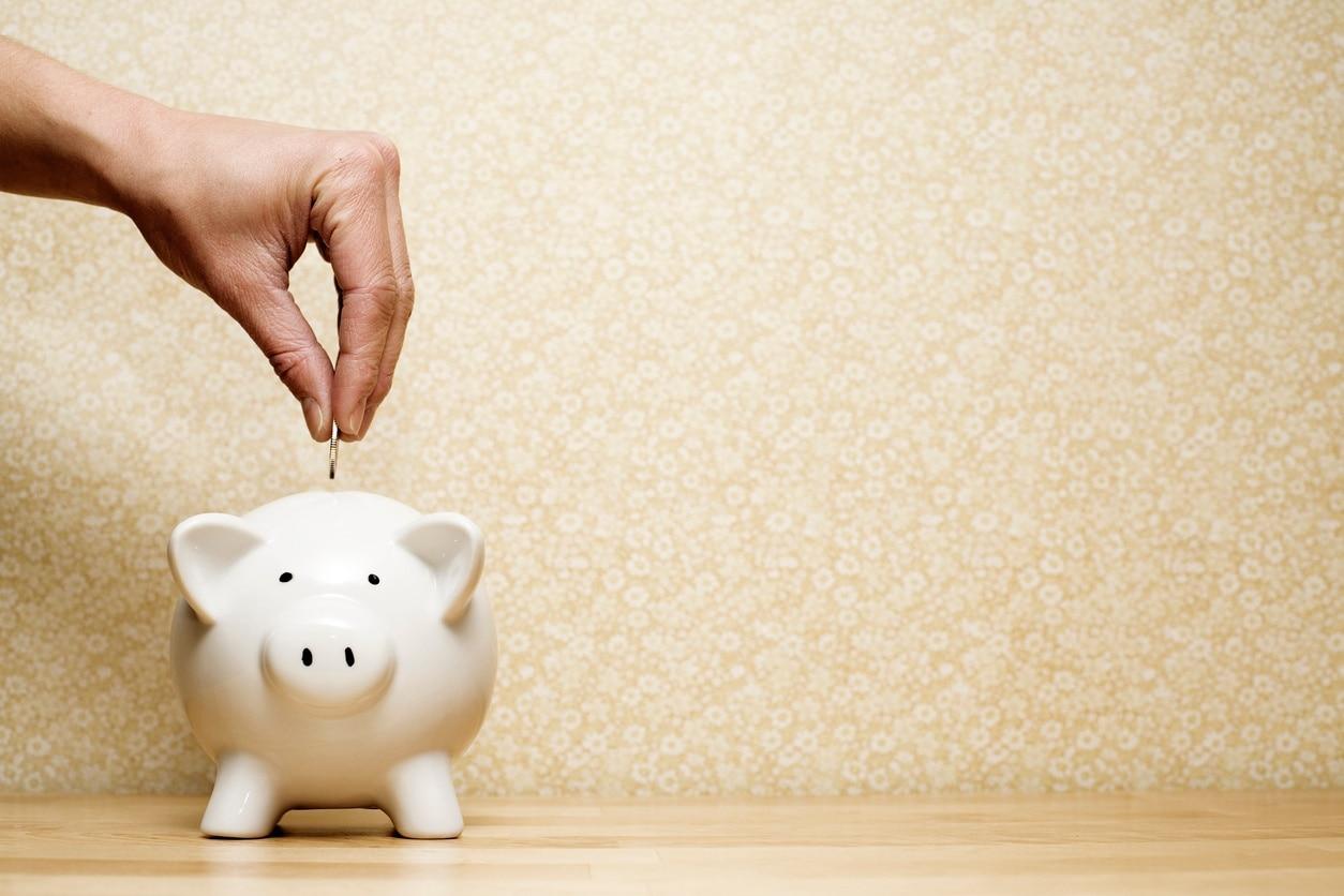 a person's hand deposits a coin into a piggy bank