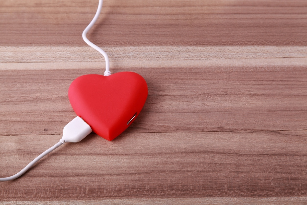 a computer power cord plugged into a heart-shaped pillow