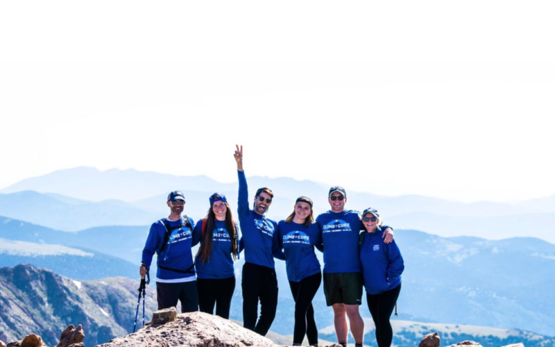 Six people standing on a mountaintop, smiling and celebratory