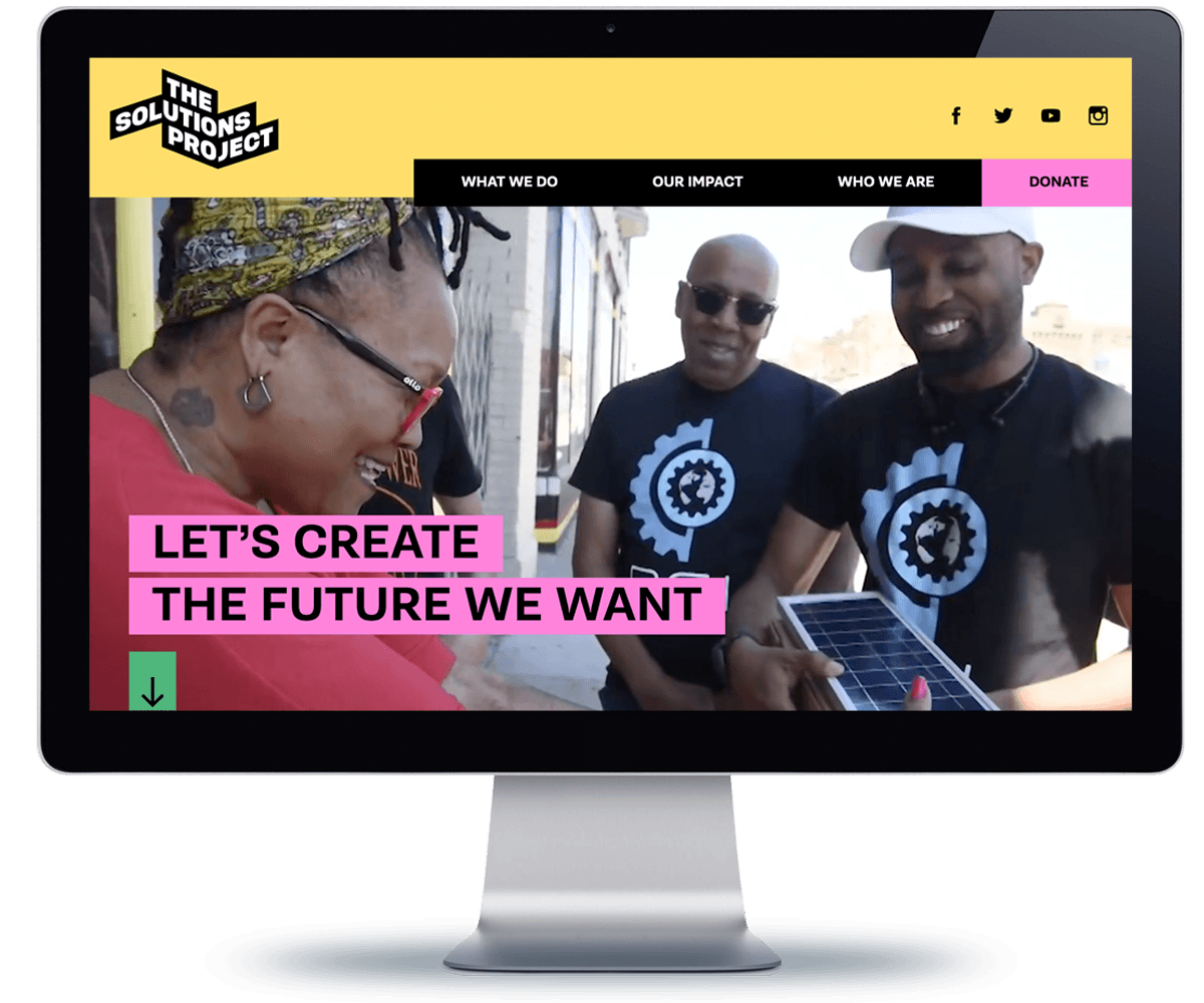 Image of the website home page on a large monitor. A happy person is accepting solar panels from two other people wearing matching logo t-shirts from a local nonprofit.