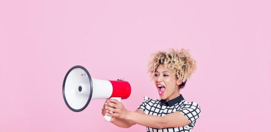 woman in business attire speaks through a megaphone