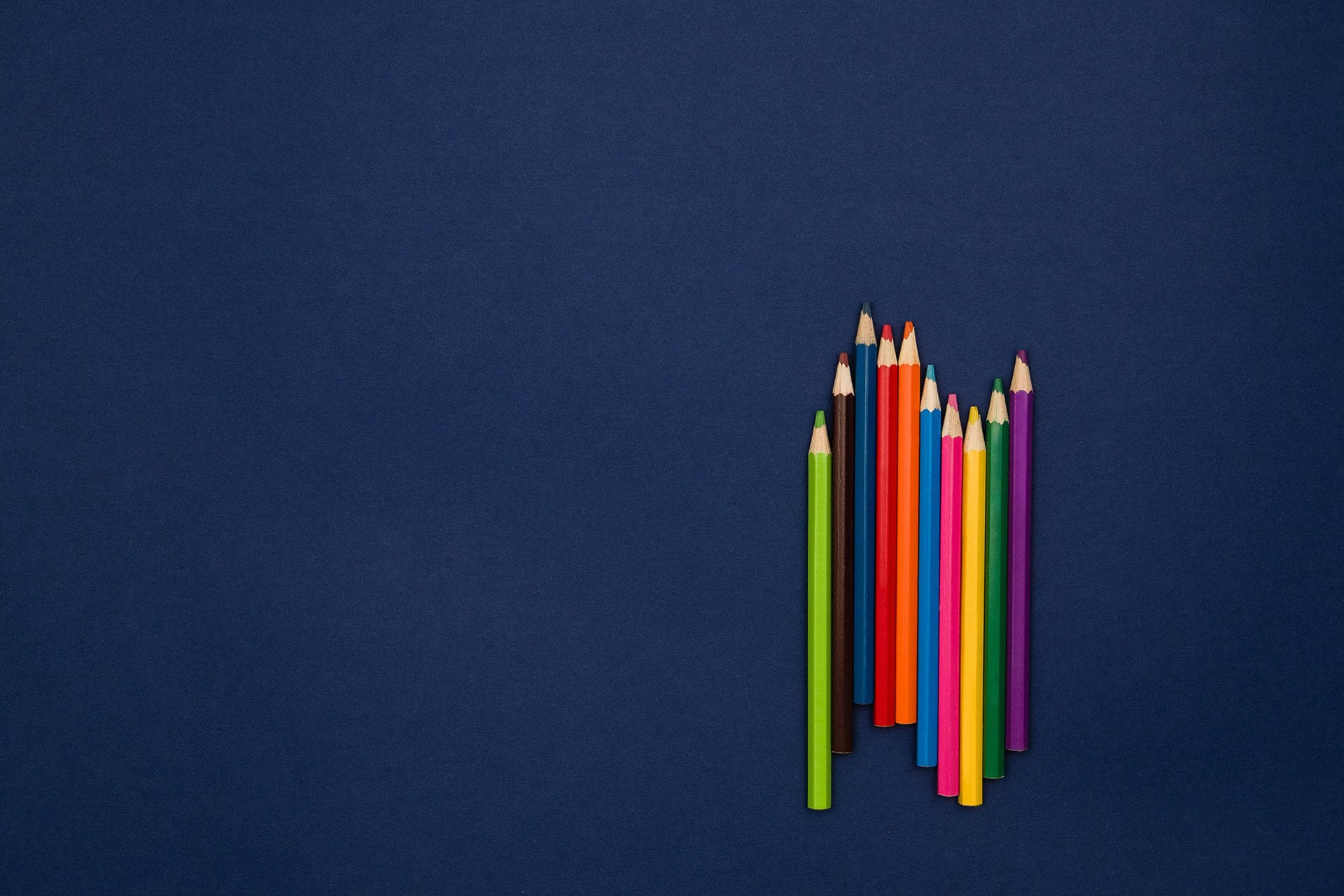 a group of colored pencils
