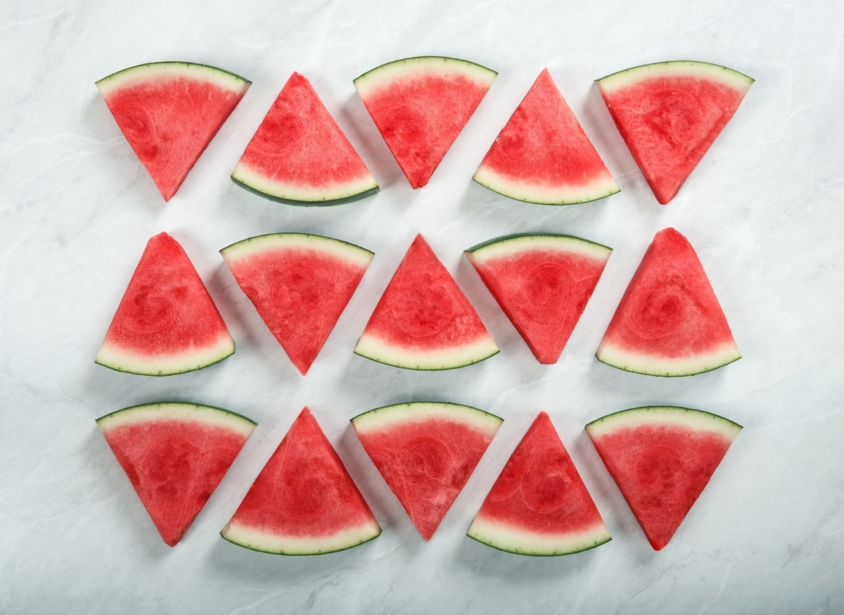 triangle shaped slices of watermelon, arranged in three rows of five