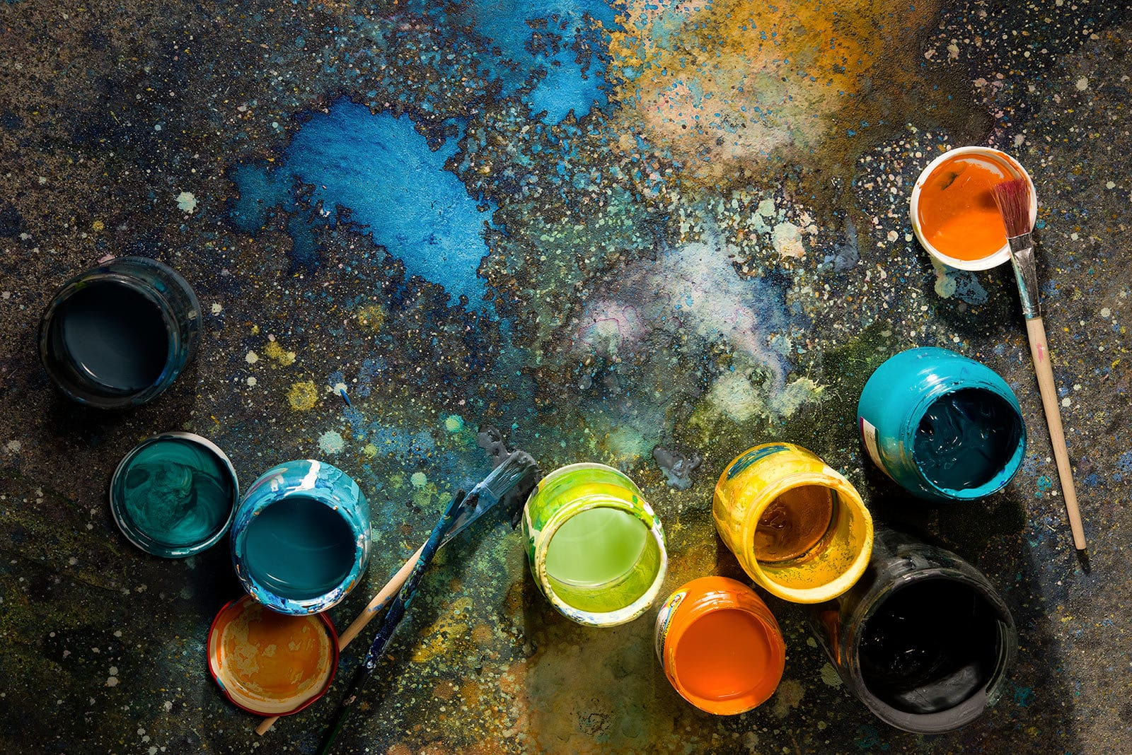 top view of colored paints in jars on the floor