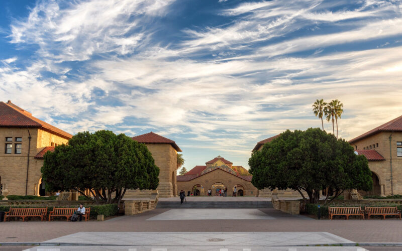Photo of the Stanford University Quad under a blue sky with fluffy white clouds