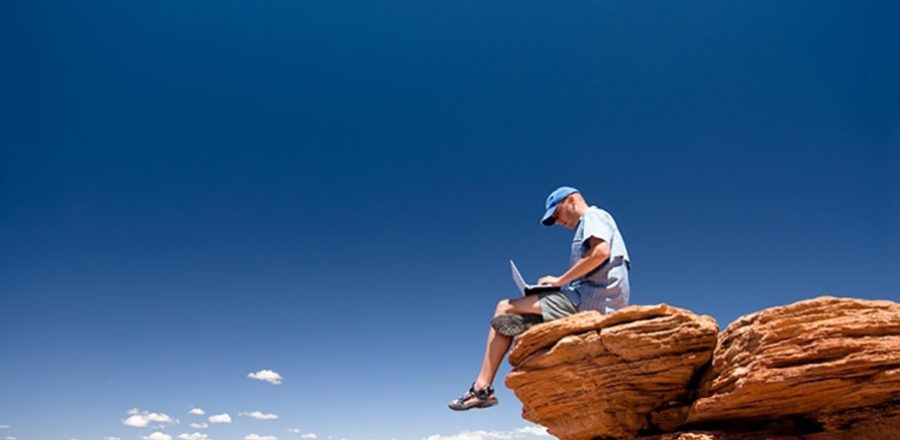 person working on a laptop atop a high mountain